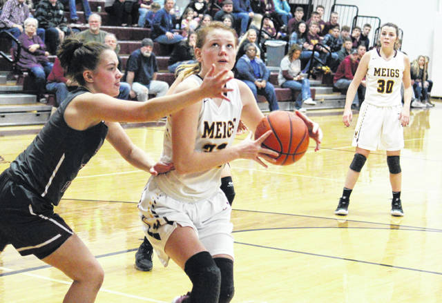 Meigs freshman Mallory Hawley (center) drives to the basket against a Vinton County defender, during the Lady Marauders' nine-point setback on Monday in Rocksprings, Ohio.