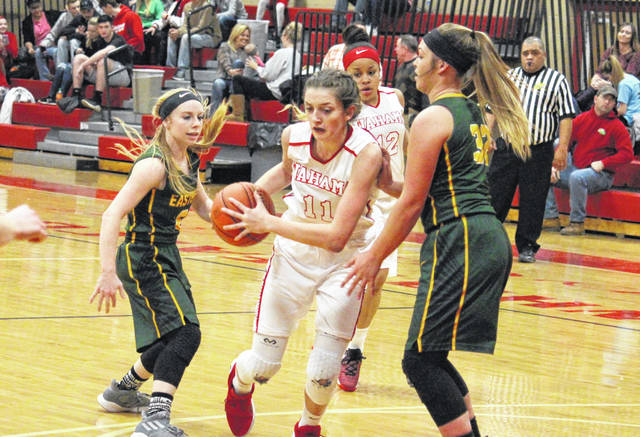 Wahama sophomore Emma Gibbs (11) drives between Eastern seniors Jess Parker (left) and Kelsey Casto (32), during the Lady Falcons 64-46 victory on Thursday at Gary Clark Court in Mason, W.Va.