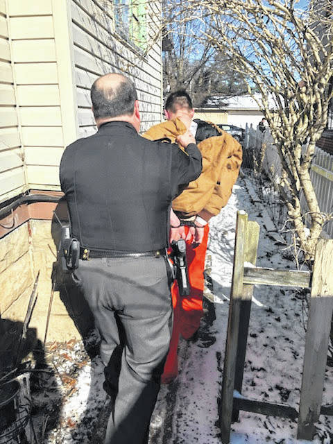 William Earl Mullins is led from a residence on Lincoln Street by Sgt. Rick Patterson after being taken back into custody.