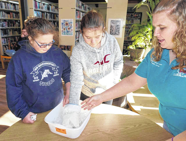 "Some animals add extra fat or blubber to maintain their heat during the cold. Pictured is Library Clerk Racheal Zerkle, right, as she helps Becky Miller, left, and Emma Northup, center, with a ""blubber glove."" The glove, filled with lard, kept the girls' hands warmer when placing them in a tub of ice water."