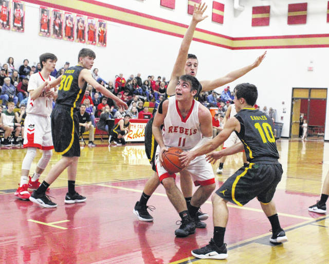South Gallia senior C.J. Mayse (11) is double-teamed by Eastern defenders Mason Dishong and Sharp Facemyer (10) during the first half of Tuesday night's TVC Hocking boys basketball contest in Mercerville, Ohio.