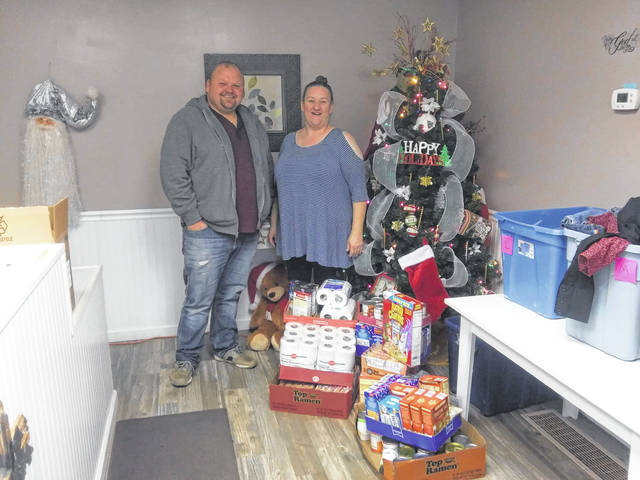 Food donations were made recently to the Cross Light of Hope Food Bank in Ashton, by the Mason County Democratic Women's Organization and the Mason County Executive Committee, which collected food and other items for several area pantries during their recent Christmas party. Presenting Teresa Wilson, right, director of the food bank with the contribution is Jason Jeffers, left, representing the organizations.