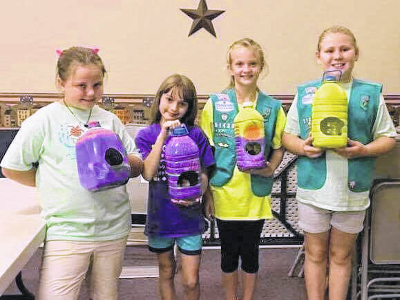 Junior Girl Scouts with their bird feeders made from up-cycled materials.
