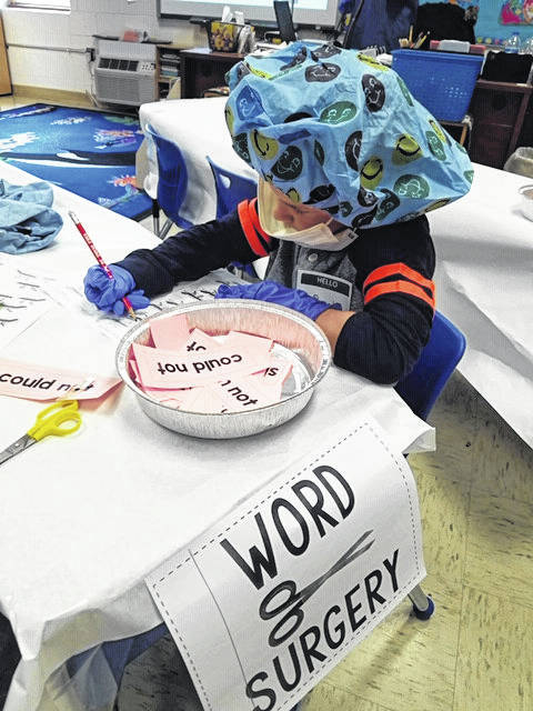 """Courtney Sayre's first grade class is pictured dressed in surgical gear while performing """"surgery"""" on their contraction words, cutting them apart and bandaging them with apostrophes."""