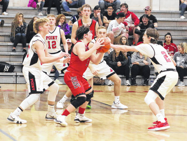 Sissonville guard Andrew Burdette is surrounded by Point Pleasant defenders Hunter Bush, Jordan Daubenmire (12), Aidan Sang and Kyelar Morrow (2) during the second half of Tuesday night's boys basketball contest at The Dungeon in Point Pleasant, W.Va.