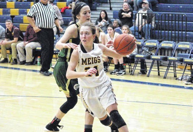 Meigs senior Madison Fields drives past Athens senior Emma Harter, during the Lady Marauders' 54-25 sectional championship victory on Thursday in Wellston, Ohio.