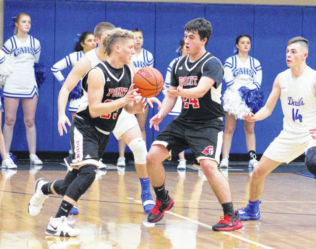 Point Pleasant junior Braxton Yates (24) hands the ball off to teammate Hunter Bush during the first half of a Jan. 5 boys basketball contest against Gallia Academy in Centenary, Ohio.