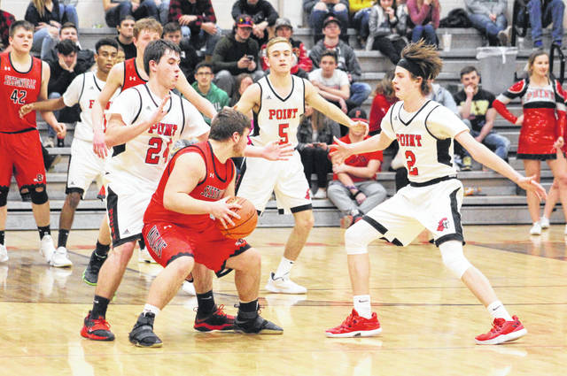 Point Pleasant defenders Braxton Yates (24) and Kyelar Morrow (2) apply pressure to a Sissonville player during the second half of Tuesday night's Class AA Region IV, Section 1 basketball contest in Point Pleasant, W.Va.