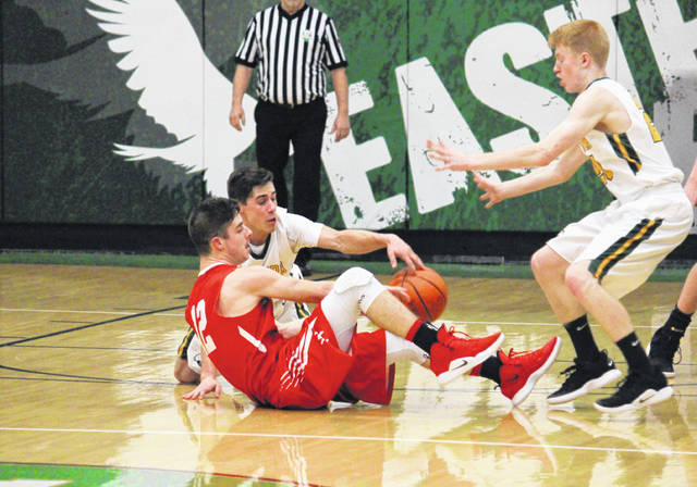 Eastern senior Sharp Facemyer steals the ball in front of teammate Ryan Dill (right) and Wahama junior Abram Pauley (12), during the Eagles' 37-36 victory on Tuesday in Tuppers Plains, Ohio.