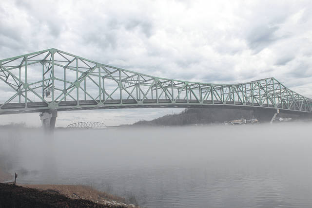 Fog rises above the Kanawha River just before it dumps into the Ohio this week near the Bartow Jones Bridge connecting Point Pleasant and Henderson.