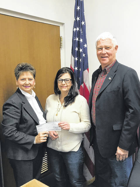 Pictured are County Clerk Diana Cromley and Mason County Commission President Rick Handley presenting Lorrie Wright, WVU extension agent, with a donation from the county for the 4-H Dining Hall renovations.