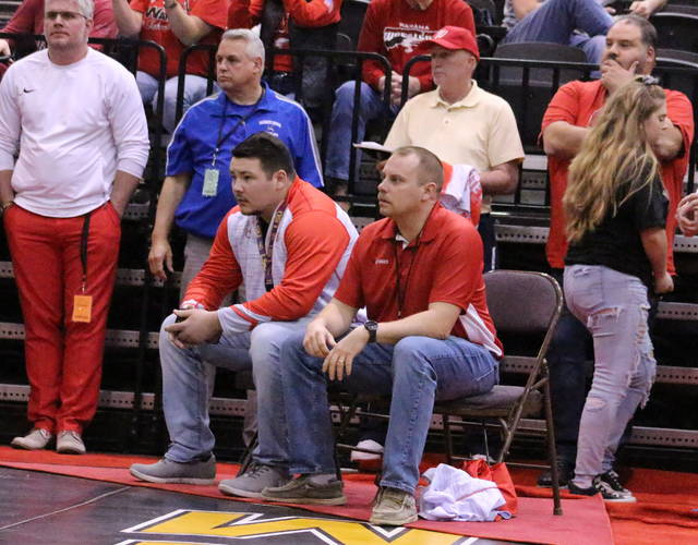 Wahama wrestling head coach Ryan Russell, seated right, watches along with assistant coach Demetrius Serevicz during Thursday night's opening round matches of the 2019 WVSSAC Wrestling Championships being held at Big Sandy Superstore Arena in Huntington, W.Va.