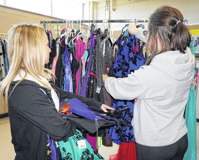 "Two students are pictured as they help hang prom dresses on a rack at ""Wings N' Things,"" located inside Wahama High School. The clothing closet is available to all students, regardless of parents' income."