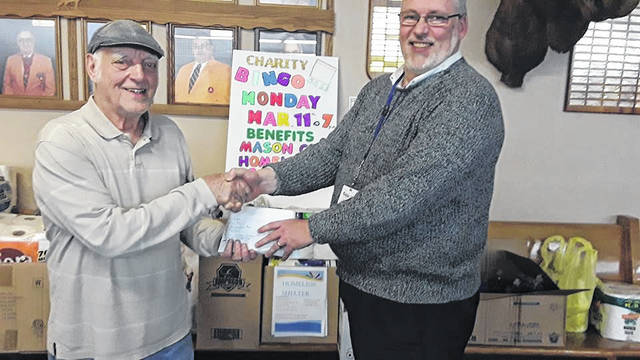 Pictured are, from left, Ray Armentrout of the lodge giving John Machir, housing director of the Mason County Homeless Shelter and Simms housing, the profits from a recent charity bingo.