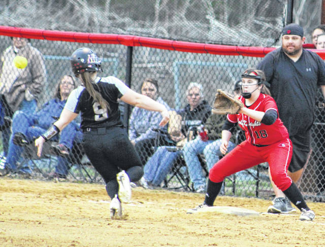 Point Pleasant freshman Emma Harbour (18) waits for a relay throw at third base as River Valley senior Baylee Hollanbaugh (9) starts a slide attempt during the first inning of Thursday night's softball contest in Point Pleasant, W.Va. Hollanbaugh was tagged out on the play.
