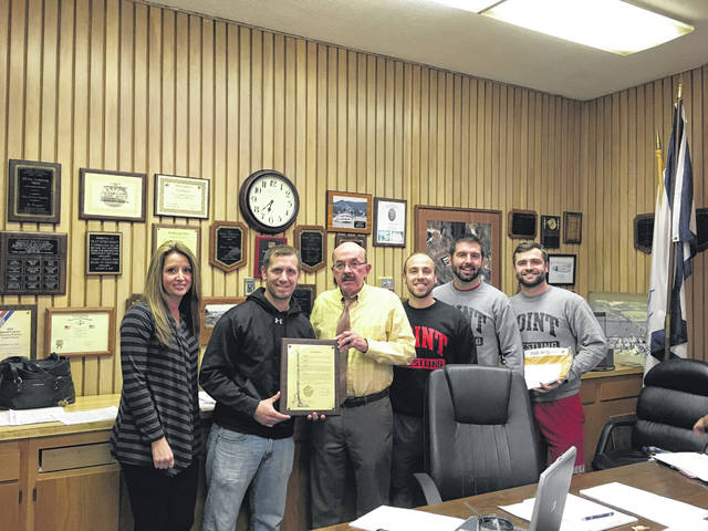 Point Pleasant City Council recently recognized the Point Pleasant Big Blacks wrestling team for the team's achievements at the WVSSAC (West Virginia Secondary School Activities Commission) Wrestling Championships. Pictured are Mayor Brian Billings and City Clerk Amber Tatterson presenting Head Coach John Bonecutter and his assistants Jed Ott, David Bonecutter, and James Casto with a commemorative plaque.