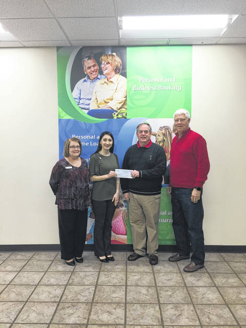 Roxanne Weaver and Valerie Johnson present the Peoples Bank donation towards the Gold Star Mothers Monument to Ed Cromley and Rick Handley.