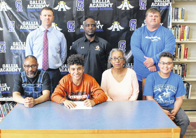 Gallia Academy senior Jason Stroud, seated second from left, will be continuing his wrestling career after signing with Lourdes University after signing a letter of intent on Monday, April 8, 2019, in the GAHS library. Joining Jason at the table are parents David and Marica Stroud, as well as brother Shane Stroud. Standing in back are GAHS Athletic Director Adam Clark, Lourdes wrestling coach Dock Kelly and GAHS wrestling coach Todd May.
