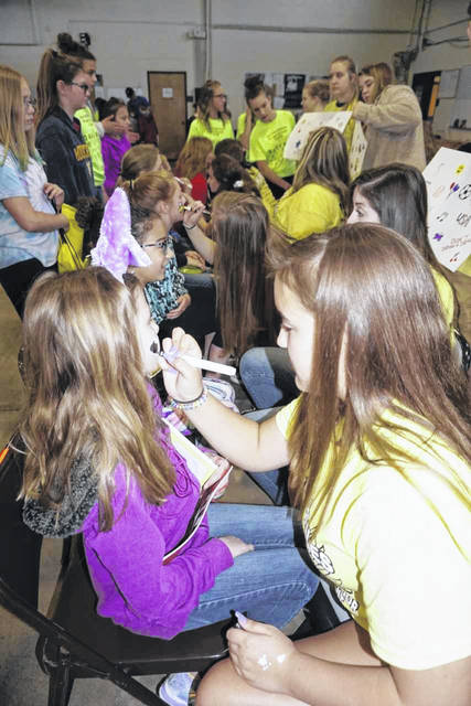 "High school participants of ""Andrea's Army"" are pictured as they paint the faces of the students attending the Mason County Outdoor Youth Expo Tuesday morning."