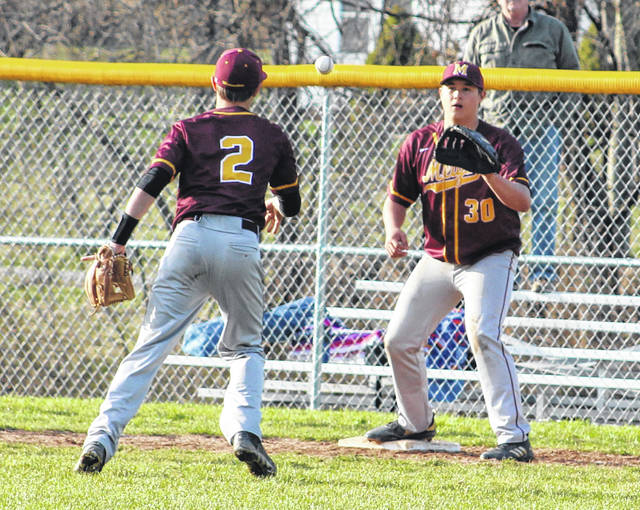 Meigs freshman first baseman Andrew Dodson (30) waits on a underhand throw by teammate Tyler Tillis (2) during the fifth inning of Monday night's TVC Ohio baseball contest against River Valley in Bidwell, Ohio.