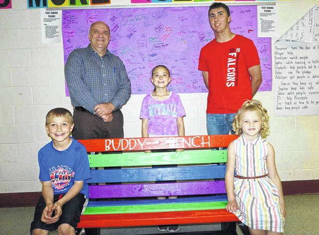 "Jacob Fisher, back row right, recently presented a ""buddy bench"" to New Haven Elementary School Principal Walter Raynes, back left, for the playground. Fisher, a student at Wahama, built the bench as part of his senior capstone. Also pictured are students Harrison Lloyd, Addy VanMeter, and Kabella Ord, from left."