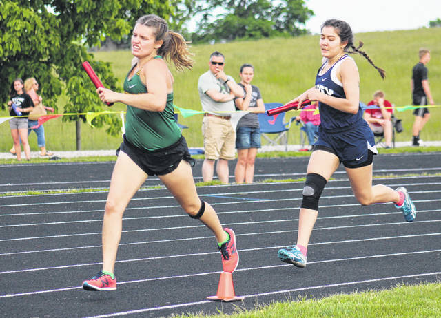 Eastern senior Ally Durst (left) leads Carey's Nellie Bianchi in the first leg of the 4x800m relay at the Region 11 championships on Wednesday in Rushville, Ohio.
