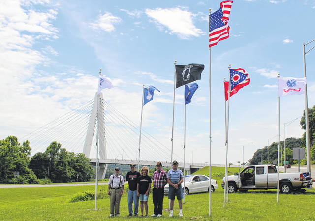 New flags were placed at the Bridge of Honor last week, a collaborative effort between the Drew-Webster American Legion Post 39 and the Aanestad Family. Pictured (from left) are Dan Arnold, Sam VanMatre, Jane Ann Aanestad, Steve VanMeter and Wayne Thomas.
