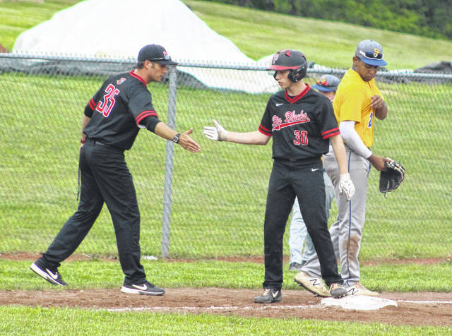 Point Pleasant junior Hunter Blain, right, gets a congratulatory hand slap from head coach Andrew Blain after reaching third base on an error during the fifth inning of Wednesday night's baseball game against Huntington Saint Joseph in Point Pleasant, W.Va.
