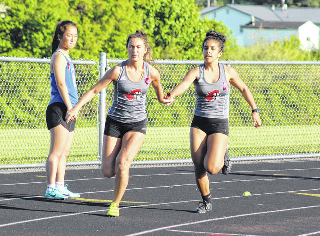 Point Pleasant seniors Teagan Hay, left, and Sydnee Moore complete a baton exchange in the 4x200m relay event at the 2019 Battle for the Anchor meet held on May 6 at Gallia Academy High School in Centenary, Ohio.