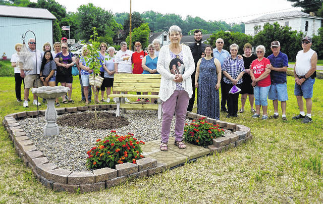 "A memorial park, in honor of the late William ""Peck"" and Lilah Zerkle, was dedicated Saturday morning by members of the Mason United Methodist Church. Pictured, in front, is the Zerkle's daughter, Claudia Thomas, holding a photo of her parents. The park is located at the corner of Second and Horton streets, across from the church."