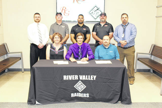 River Valley senior Eric Weber, seated front and center, will be continuing his track and field career at the University of Rio Grande after signing with the RedStorm on Wednesday, May 1, during a ceremony in the RVHS lobby. Weber is joined at the table by his parents, Jessica and Michael Weber. Standing in back, from left, are RVHS Principal T.R. Edwards, RVHS throwing coach Chuck Wood, Rio Grande assistant Alex Nichols, Rio Grande throwing coach Burt Wood, and RVHS Athletic Director Richard Stephens.