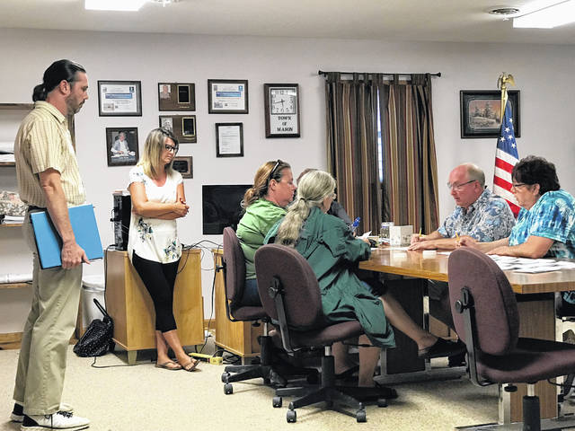 Mason mayoral candidate Heath Engle, left, and Incumbent Mayor Donna Dennis, also standing, are pictured as they watch the recount team tally the results from the June 11 municipal election, following Engle's recount request. Council members were able to certify the results when the final tally showed 69 votes for Dennis and 66 for Engle.