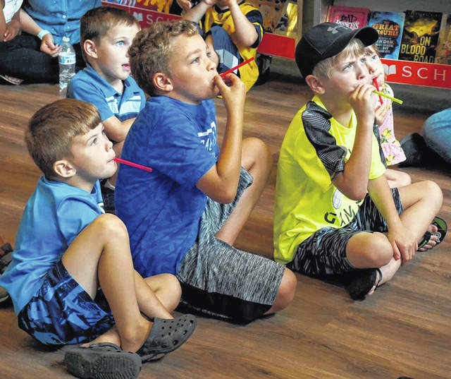 "Children attending the program, ""The Science of Sound,"" at the libraries Monday learned how to make kazoos from plastic straws. They were used to play along with Tony M. Music."