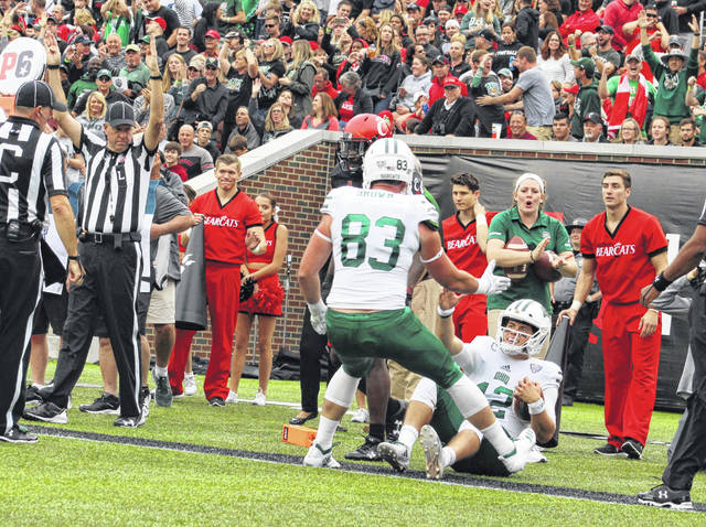 Ohio quarterback Nathan Rourke (12) receives a helping hand from teammate Connor Brown (83) after scoring a second quarter touchdown against Cincinnati during a Sept. 22, 2018, non-conference game at Nippert Stadium in Cincinnati, Ohio.