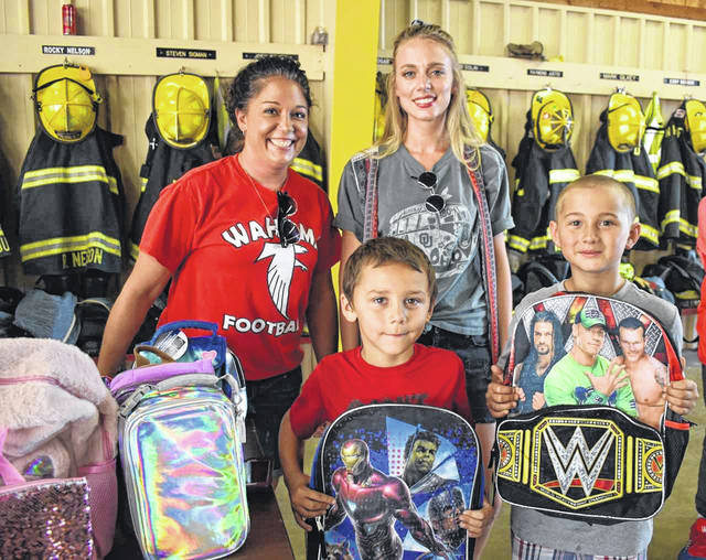 Over 100 backpacks and lunch boxes, full of school supplies, were given to children attending the New Haven Back-to-School Bash on Thursday. Pictured receiving backpacks are Bryson Laudermilt, left, and Jayden Laudermilt. Handing out the goodies were Jessica Greene, back left, and Michaela Davis.