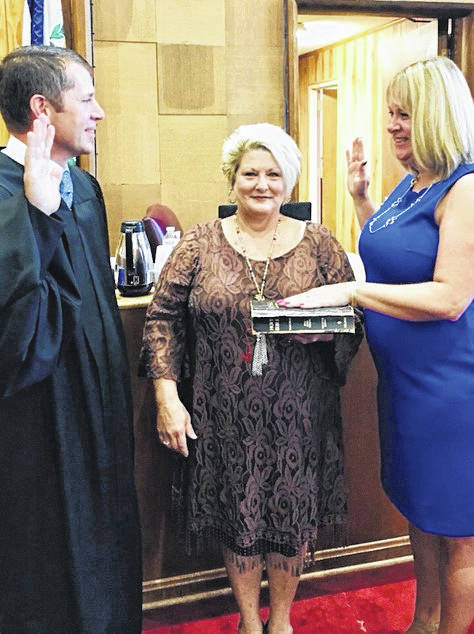 Judge R. Craig Tatterson, far left, administers the oath of office to Magistrate Melanie Sang, far right, while outgoing Magistrate Gail Roush holds the Bible.