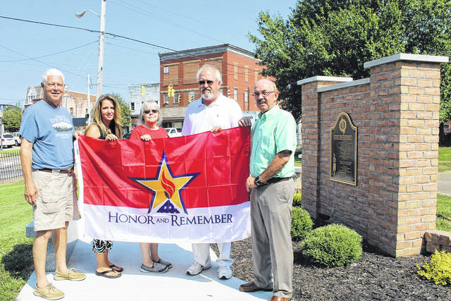 An Honor and Remember Flag, which was presented to Point Pleasant City Council from representatives from the West Virginia Gold Star Mothers organization is now flying high near the Gold Star Mothers Monument in the courtyard of the Mason County Library in Point Pleasant. On Tuesday, Mayor Brian Billings and City Clerk Amber Tatterson presented the flag to County Commissioner Rick Handley to be placed in the courtyard which is owned by the county. For now, the flag hangs on the existing flagpole but the plan is to eventually place it on another flagpole at the monument. Pictured with the flag, from left, are Handley, Tatterson, Pam Thompson, library director, Denny Bellamy, tourism director, Billings.