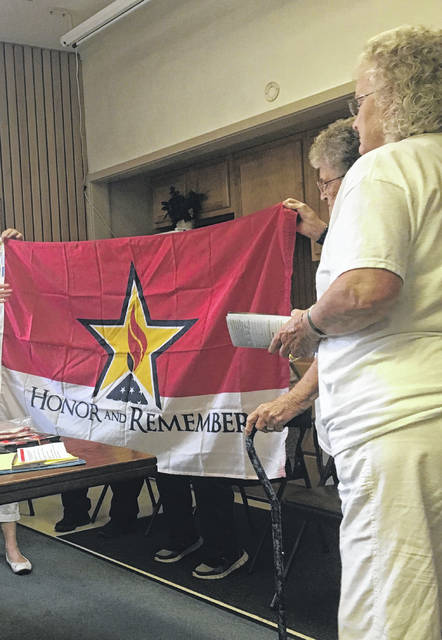 WVGSM members Shirley White, Emma Johnson, Belinda Jividen, and Barbara Ulbrich explain the meaning of Honor and Remember Flags at the Point Pleasant City Council meeting on Monday evening.