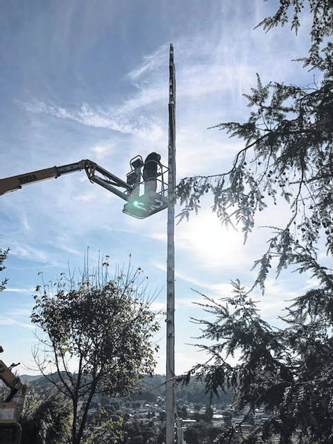 Brian Grindstaff works to replace the bulbs and electrical on the cross located off Riverview Drive on the hill above Pomeroy.