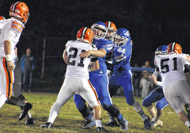 Gallia Academy senior Zac Canaday (center) stops Ironton senior Richard Thompson (21) near the line of scrimmage, during the Fighting Tigers' 52-0 victory on Friday at Memorial Field in Gallipolis, Ohio.