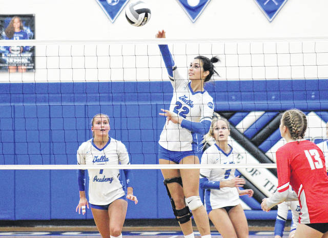 Gallia Academy senior Maddie Wright (22) spikes the ball in front of classmates Peri Martin (left) and Alex Barnes (5), during the Blue Angels' season-ending setback on Oct. 23 in Londonderry, Ohio.