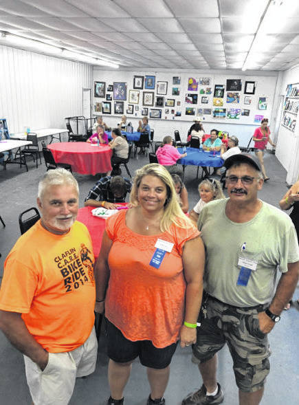 """Robert and Louise Claflin Foundation Vice President Gary Fields, pictured on the left, along with Mason County Fair Treasurer Nikki Hunt, and Mason County Fair President Shawn Paugh enjoying a """"cool down"""" in the Mason County fairground's cooling room."""