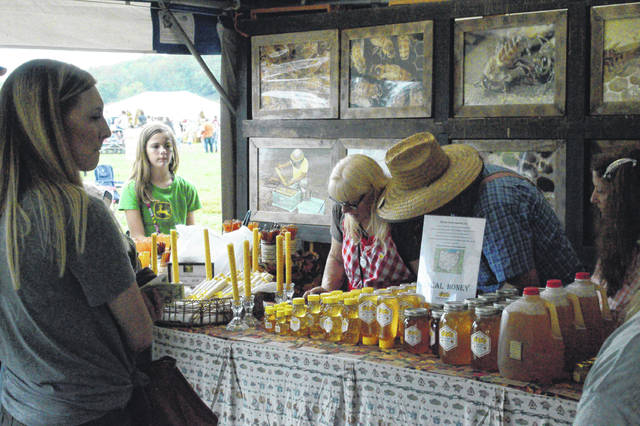 Merchants share their honey with farm festival visitors.