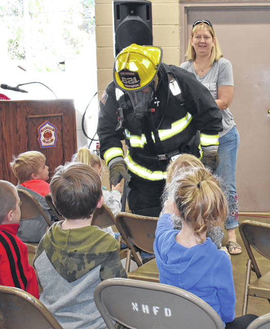 New Haven Firefighter Steven Sigman, dressed in full bunker gear, is shown as he greets each student individually at the fire station Wednesday. The firemen want the children to know what they look and sound like so they won't be afraid in case of emergency. Also pictured is Lisa Gangwer, longtime volunteer.