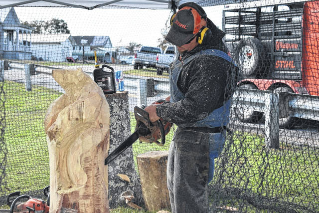 A professional chainsaw carver from the Mason Dixon Boys, LLC is pictured as he begins carving a black bear at the Mason Harvest Festival Saturday.