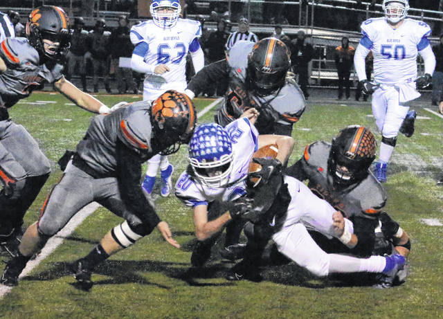 Gallia Academy junior Michael Beasy (20) is swarmed by a trio of Waverly defenders during a first half carry Saturday night in a Division IV, Region 15 quarterfinal playoff contest at Raidiger Field in Waverly, Ohio.