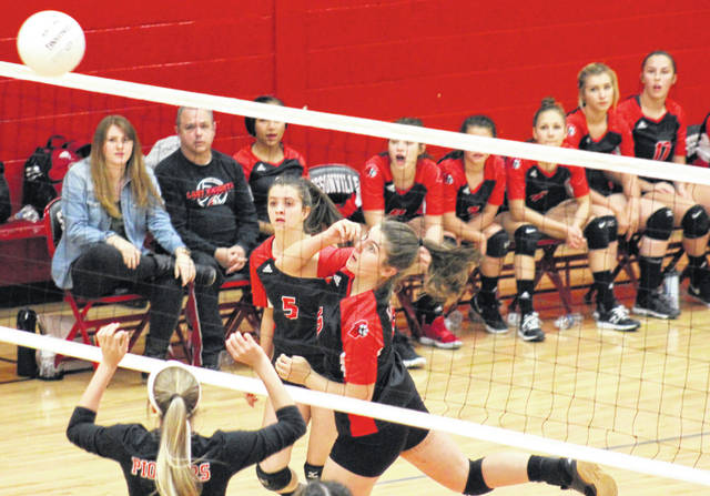 Point Pleasant senior Olivia Dotson (right) tips the ball over the net in front of teammate Brooke Warner (5), during the Lady Knights' 3-0 victory over Wayne on Monday in Sissonville, W.Va.