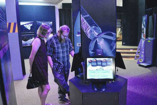 Visitors interact with SPACE: A Journey to Our Future in the Bossard Memorial Library.