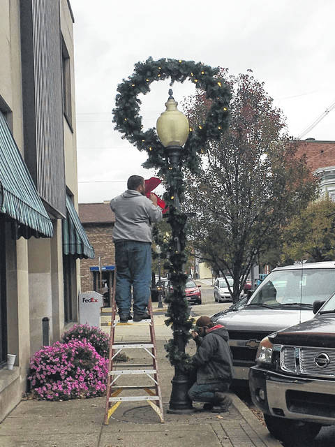 Employees with the Point Pleasant Street Department work to hang Christmas wreaths and garland to decorate Main Street on Tuesday.