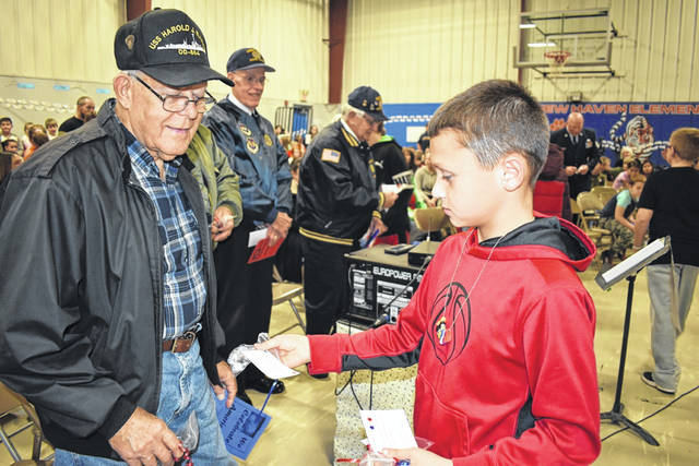 "Nate Harris, right, a fifth grade student at New Haven Elementary School, is pictured as he presents U.S. Navy Veteran Dean Knight with a favor bag of Hershey ""Hugs"" and ""Kisses,"" in appreciation of the sacrifices made by him and the other veterans in attendance."